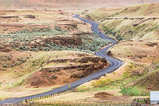 Country road winding through sage brush hills. stock photo