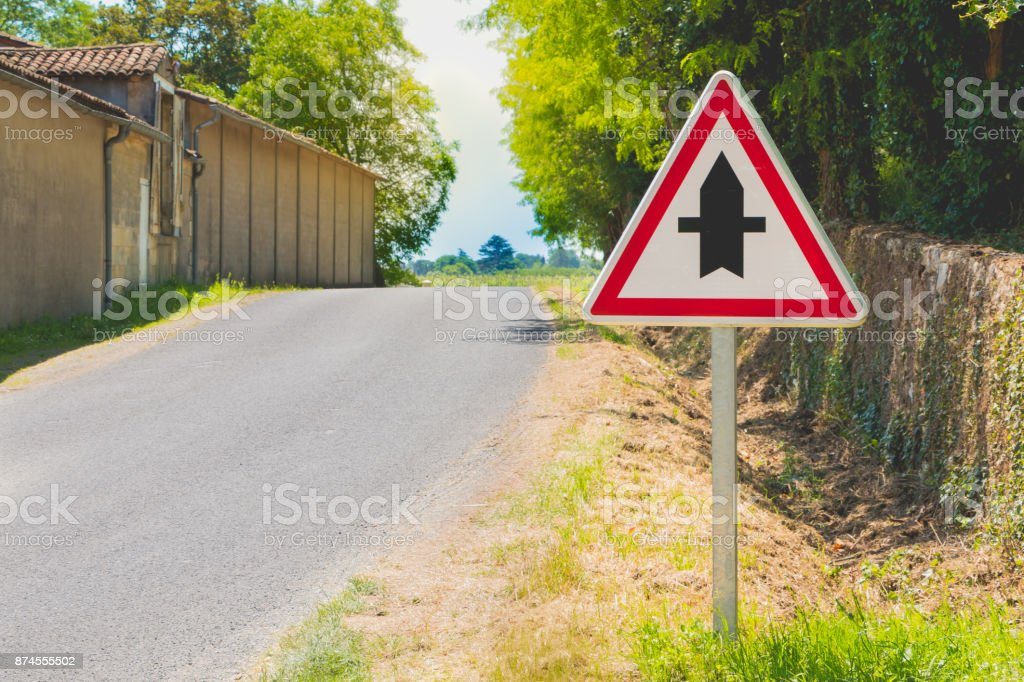 country road with a priority crossroads sign stock photo