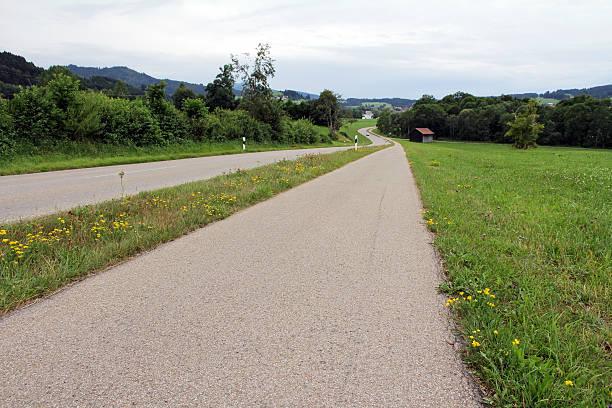 country road mit fahrrad track - radwege deutschland stock-fotos und bilder