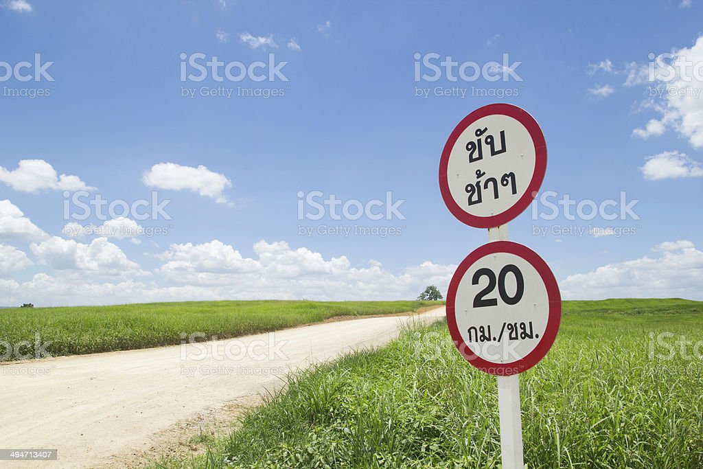 Country road with green field and 20 kilometres stock photo