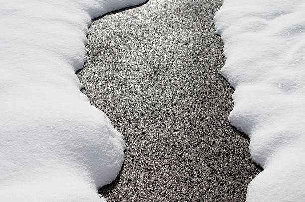 country road with melting snow - snow pile stock photos and pictures