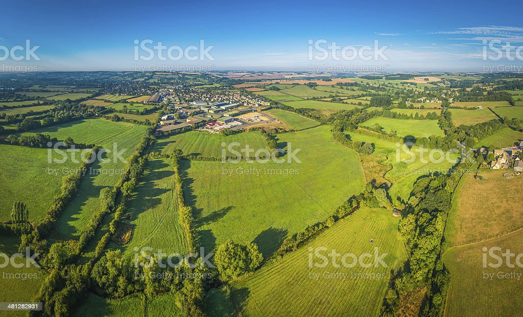 Country town in patchwork pasture landscape summer green fields panorama stock photo