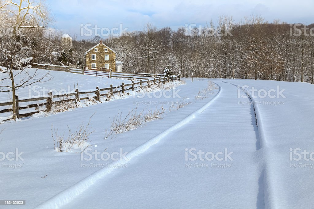 Country Winter - Snow-Covered Railroad Tracks by Old Stone Farmhouse stock photo