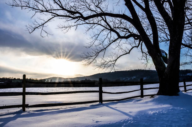 countryside field in virginia covered in snow during winter sunset - ash united stock-fotos und bilder