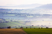 Rolling countryside in early morning mist in Monmouthshire, UK