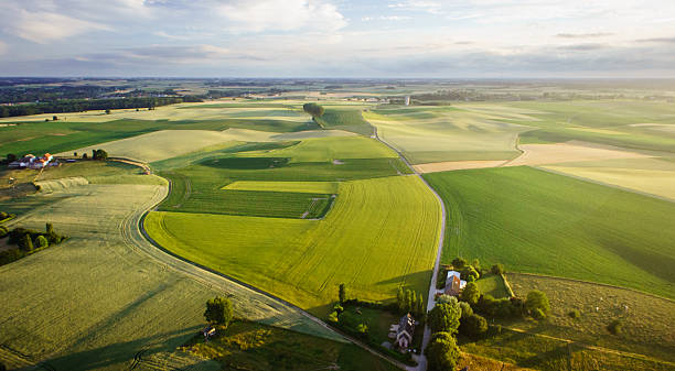 Countryside landscape from a drone at sunset Picture of a countryside landscape, showing cultivated land and fields, with farmhouses in the back. Picture taken from the air with a drone, at sunset, giving a warm and low light with high color contrasts and shadows in the fields. cultivated land stock pictures, royalty-free photos & images