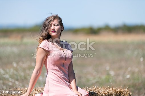 istock Countryside landscape in Tuscany, Italy with young girl woman sitting on hay bale in dress with hair in wind posing model 1138214974