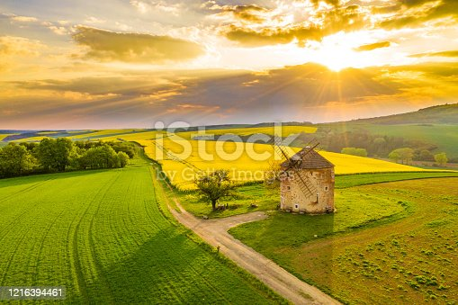 Drone point of view shot of an idyllic countryside landscape with view of the exterior of a traditional windmill and a vibrant yellow rapeseed field under a moody sky at sunset, Moravia, Czech Republic