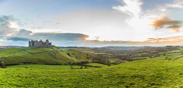 Countryside panorama with ruined castle on a hill at sunset Countryside panorama with ruined castle on a hill. Welsh scenery at sunset, panoramic photo, with green meadows on foreground. Nature and travel concepts wales stock pictures, royalty-free photos & images