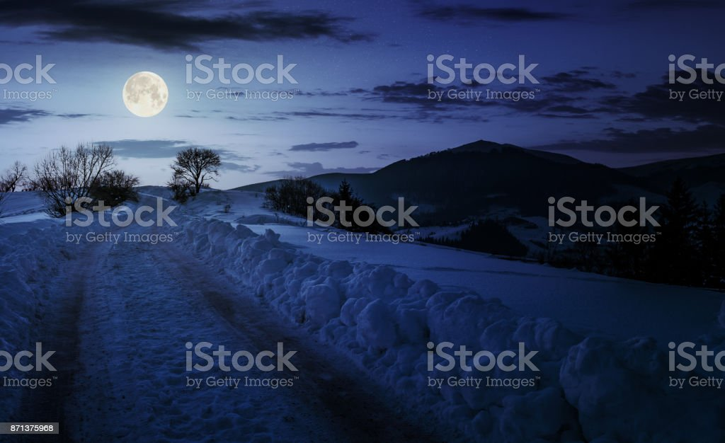 countryside road uphill in snow at night stock photo