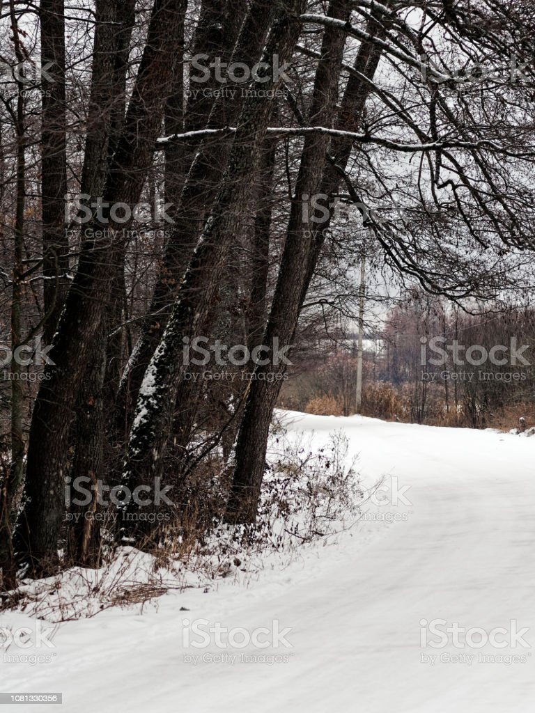 Slippery countryside street covered with melty snow. Thaw in winter