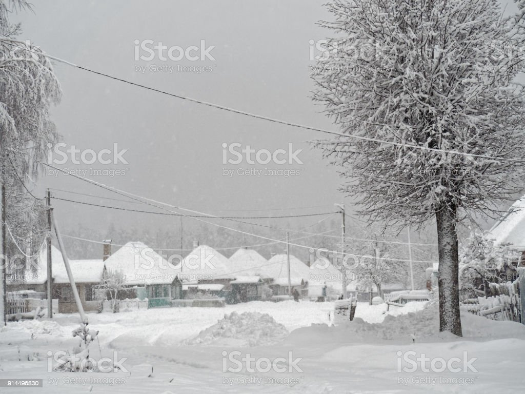 Countryside street covered with deep snow. Strong snowfall is still...