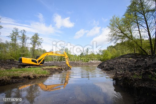 istock Countryside view of a drainage canal system and working excavator 1277187910