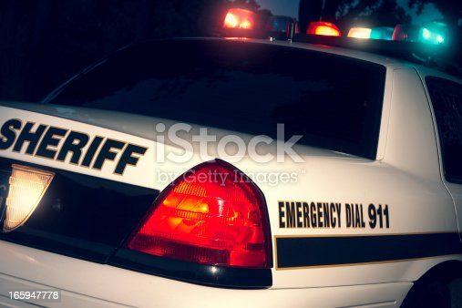 A Sheriff at the scene of a crime. Lights are flashing. Note: image is cross-processed.
