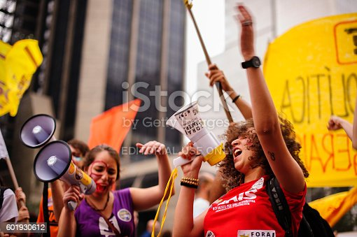 São Paulo, Brazil, September, 11, 2016: Woman with a megaphone shouting slogans during act against the coup and calling for new elections and other social agendas for the country
