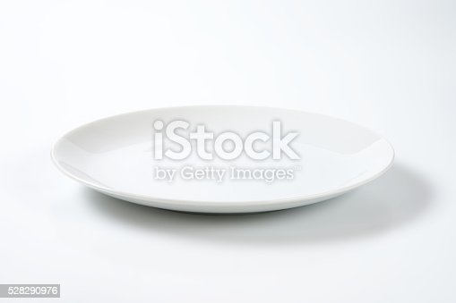 empty rimless white plate on off-white background