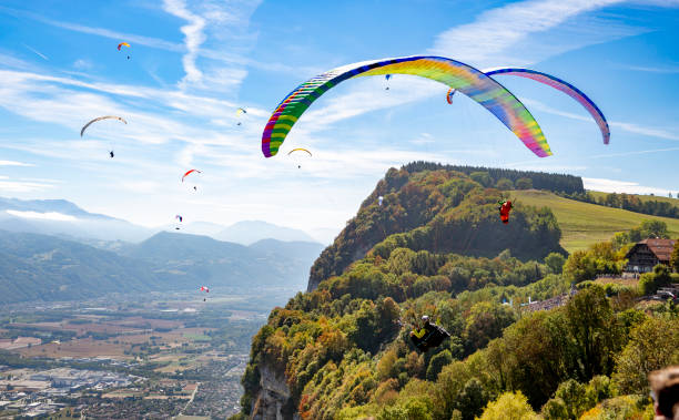 Coupe Icare, France. Acro paragliders exhibition. Paraglider pilots fly on September 22, 2018 in Saint-Hilaire-du-Touvet, south-eastern France, during the 45th Icarus cup. Created in 1974, the Coupe Icare (Icarus Cup) is the oldest 'free flight' festival in the world. It brings together more than 8.000 pilots of all kinds of aircrafts, from paragliders and hang gliders to hot air balloons and even a man in a jet-propelled suit. In this photo, paragliders make an exhibition fly. paragliding stock pictures, royalty-free photos & images