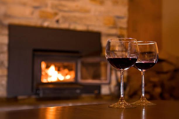 Coupes de vin sur une table devant un feu Deux coupes de vin ou de porto, sur une table devant un foyer de pierre dans une maison, un chalet feu stock pictures, royalty-free photos & images