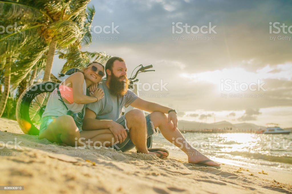 A couple - a bearded man and his handsome girlfriend - sitting on the beach leaned on motorbike, watching sunset at the sea stock photo