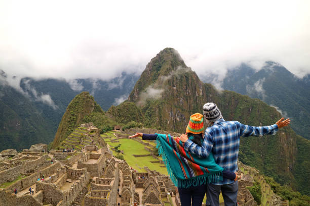 Couple admiring the spectacular view of Machu Picchu, Cusco Region, Urubamba Province, Peru, Archaeological site, UNESCO World Heritage stock photo