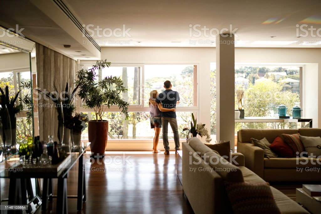 Couple admiring the view from the living room of their house. - Foto stock royalty-free di Adulto