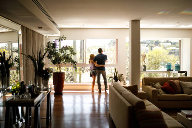 Couple admiring the view from the living room of their house. stock photo