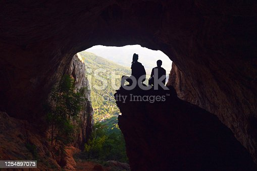 Young woman and young man in cave mountain sitting and looking at the view.