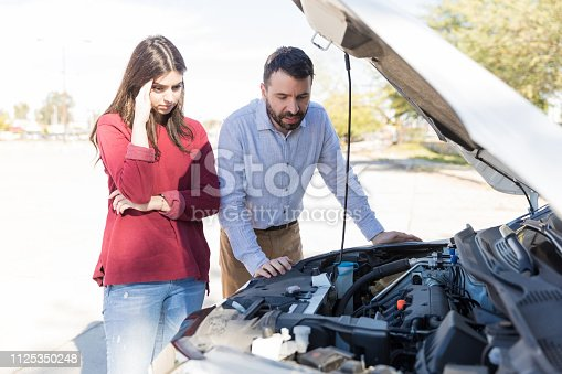 Upset young woman standing by man checking engine of broken car on road