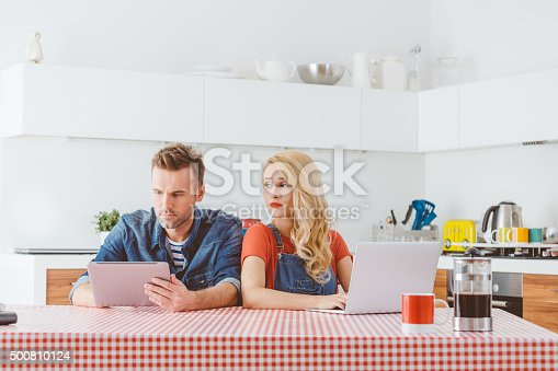 488389267istockphoto Couple after argument, man using a digital tablet, woman laptop 500810124