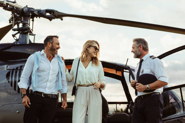 Couple alighted from a helicopter thanking pilot Smiling couple alighted from a private helicopter talking to the pilot. Couple getting off a private aircraft with mature pilot. high society stock pictures, royalty-free photos & images