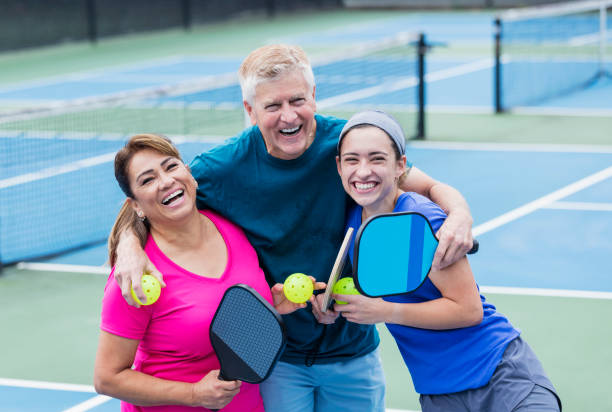 Couple and adult daughter playing pickleball stock photo