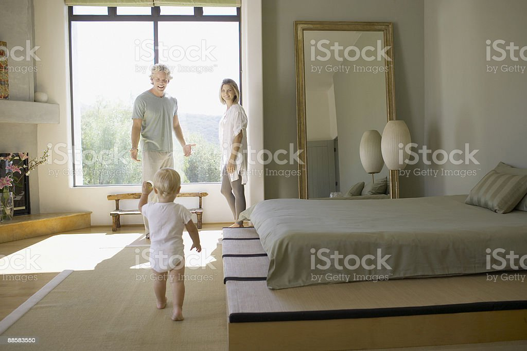 Couple and baby in bedroom stock photo