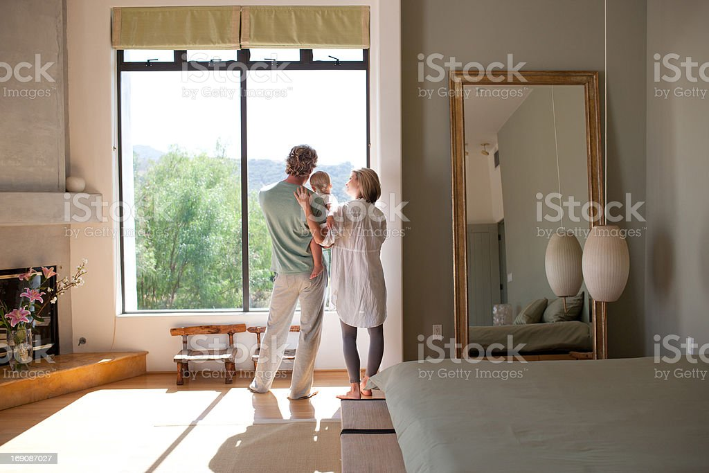 Couple and baby son looking out window stock photo