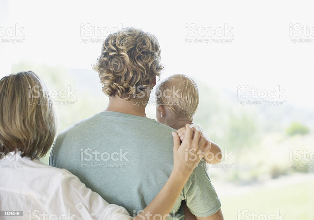 Couple and baby son looking out window royalty-free stock photo