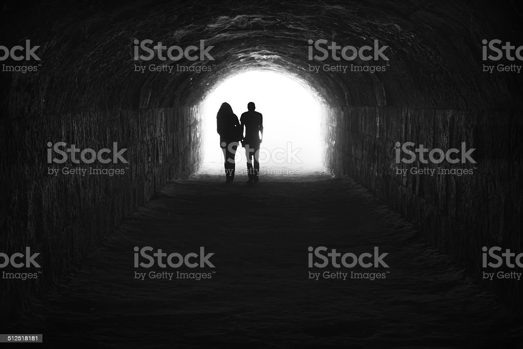 Couple and light in the end of the tunnel stock photo