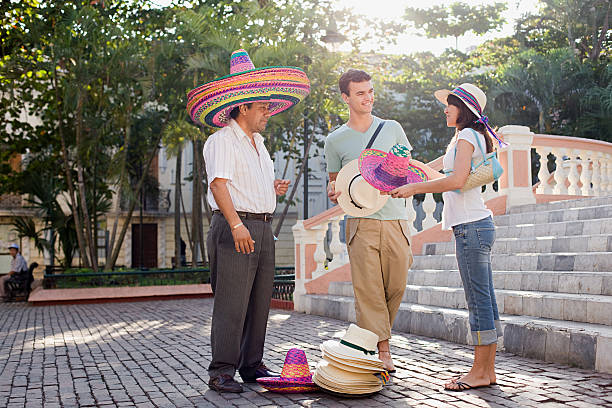 Couple and man selling hats stock photo