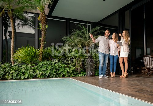 Couple and real estate agent looking at a luxury property all looking very happy and smiling