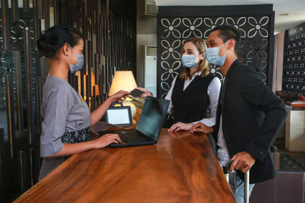couple and receptionist at counter in hotel wearing medical masks as precaution against virus. couple on a business trip doing check-in at the hotel - hotel checkin foto e immagini stock