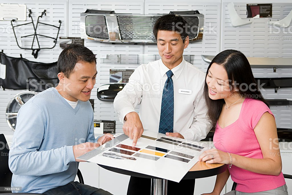 Couple and salesman at car dealership 免版稅 stock photo