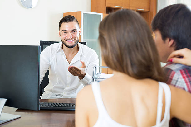 Couple and salesman talking about contract Couple and salesman talking cheerfully about contract in the office kantoor stock pictures, royalty-free photos & images