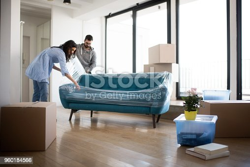 Young heterosexual couple moving out of the apartment and wrapping up the sofa.