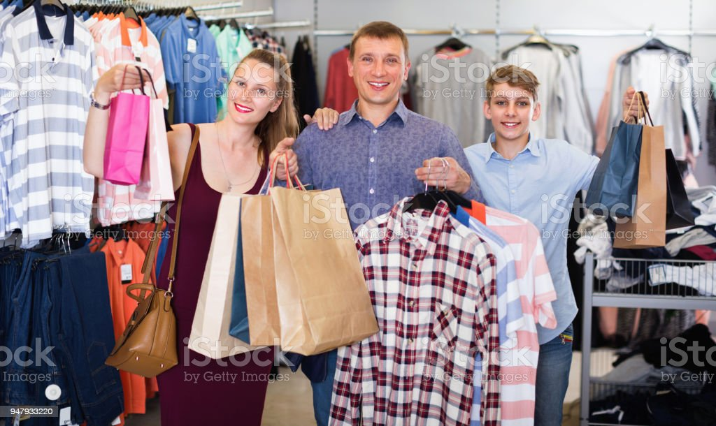 a251802e6c Couple and teenager with shopping bags with purchase in the store royalty-free  stock photo