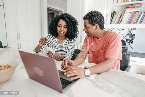 istock Couple and their financial planning in the kitchen with laptop 932392808