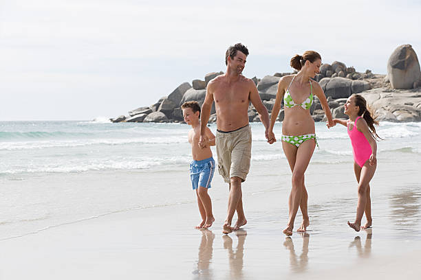 Couple and their two children strolling hand in hand along beach stock photo
