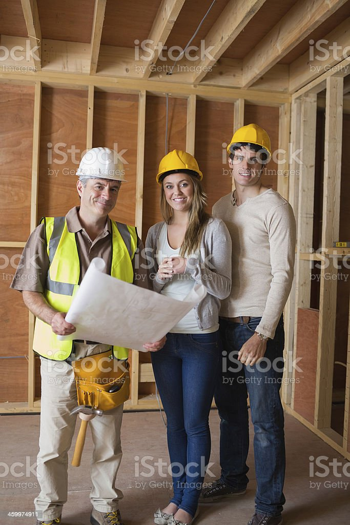 Couple and worker standing in house construction royalty-free stock photo