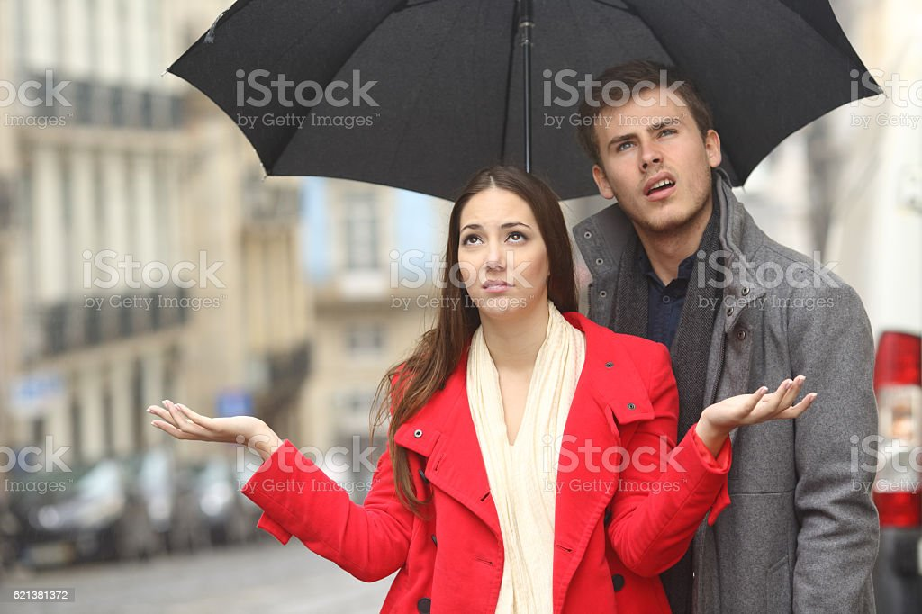 Couple annoyed in a rainy day stock photo