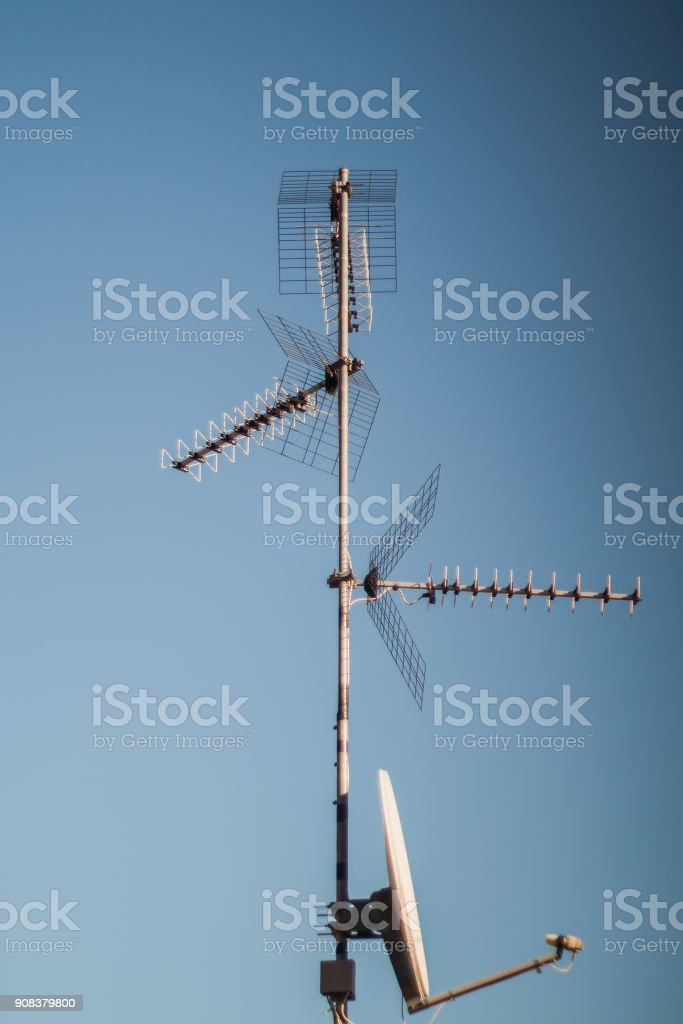 A couple antennas on the roof in good weather conditions and blue sky stock photo