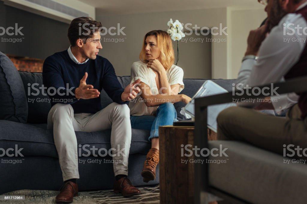 Couple faisant valoir au cours de la séance de thérapie avec une psychologue photo libre de droits
