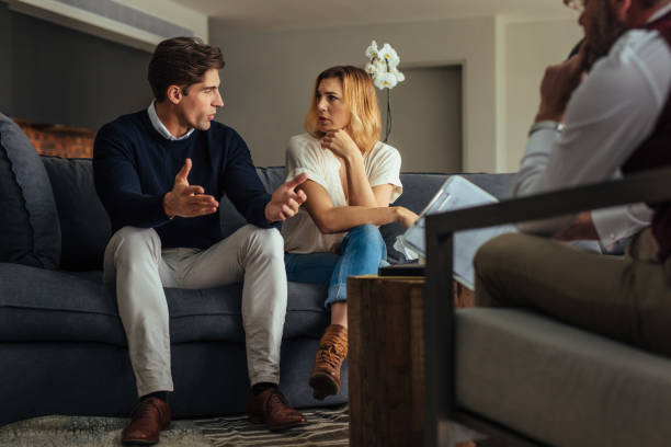 Couple arguing during therapy session with psychologist stock photo