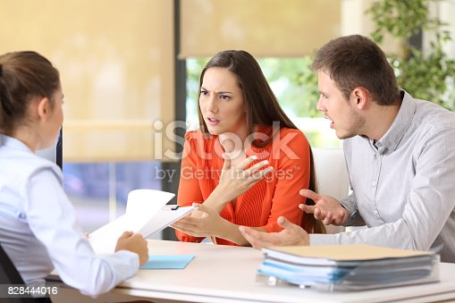 Angry couple arguing telling their problems sitting in a desktop of a marriage counseling or office